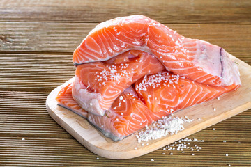 Salmon fillets with salt on a wooden background