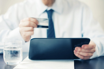 Man Holding Tablet and Credit Card.