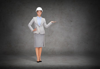 businesswoman in helmet holding something on palm