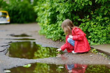Ad girl playing in a puddle on rainy summer day