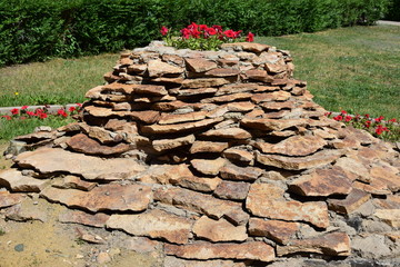 Flowerbed shaped as a small hill of schist stones