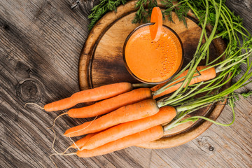 Fresh carrot juice on a wooden background