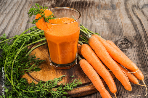 Glasses of carrot juice and fresh carrots on wooden cutting