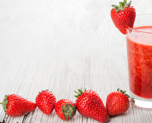 Glass with strawberry juice and berries