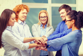 team with hands on top of each other in office