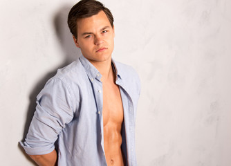 Young fit man in open shirt leaning against wall