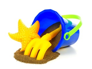 Toy sand pail with spilling sand over white