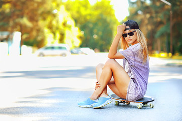 Fashion portrait of attractive girl with a skateboard
