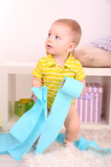 Cute little boy with toilet papers in room