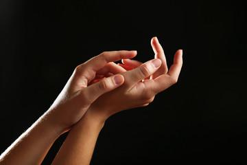 Human hands on black background