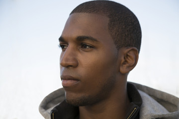 black male model wearing a hoodie with a serious expression
