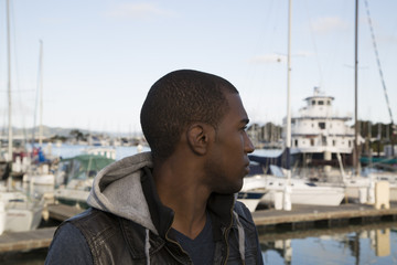 black male model looking at boats at the marina
