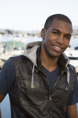 black male model portrait wearing a leather vest at the marina
