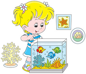 Little girl watching fishes in an aquarium