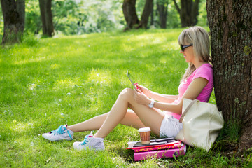 Relaxed student using tablet computer outside in park