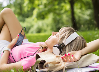 Beautiful girl enjoying music in park