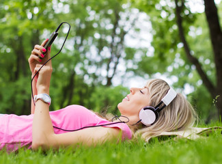 Attractive girl listening music outdoors