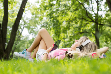 Relaxed woman listening music on headphones in park