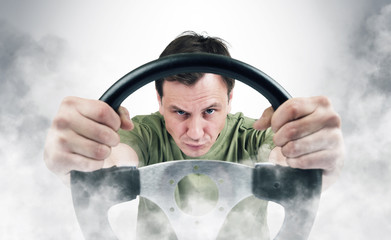 Man with a steering wheel in smoke, auto concept