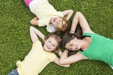 Drei Mädchen liegen im Gras