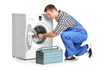 Young plumber fixing a washing machine