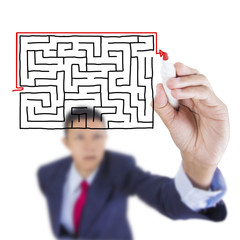 Businessman look up and writing exit from maze problem