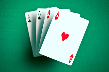 four aces on green casino table