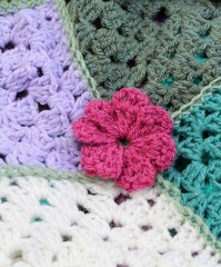 Crochet flower on patch work afghan