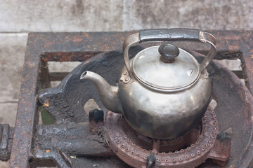 Old kettle on rusty gas stove