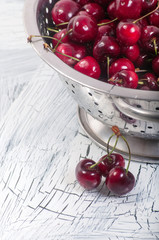 Metal colander filled with cherries over a rustic background