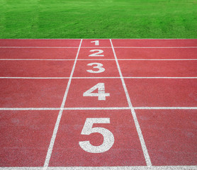 Start or finish position on running track with green field