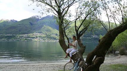 Young woman on tree by the lake with digital tablet