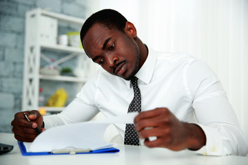 African man reading document in office