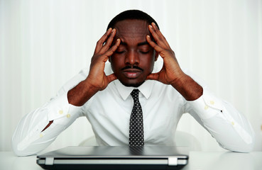 Pensive african businessman sitting at his workplace in office