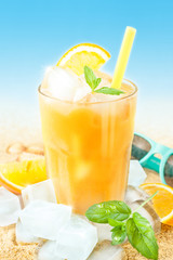 Cold orange juice with ice on beach background