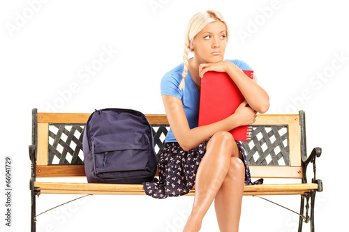 Worried female student sitting on a bench