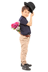 Little boy holding flowers behind his back