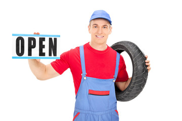 Male mechanic holding an open sign