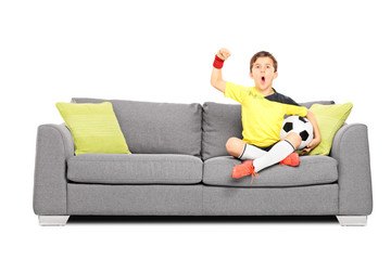 Kid cheering and holding football seated on sofa