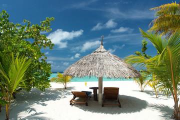 Liegestuhl mit Sonnenschirm am Strand