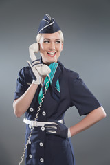 Calling retro blonde stewardess wearing blue suit. Holding white