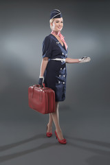Smiling retro blonde stewardess wearing blue suit. Holding red l