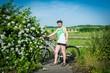 Frau mit Fahrrad auf dem Land