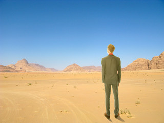 Young business man standing in African desert