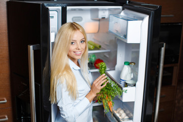 Beautiful young woman near the fridge with healthy food.