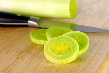 Fresh leek whole and sliced on a wooden board with knife