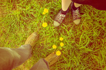 Background met a guy and a girl. Feet in the field