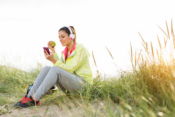 Relaxed fitness woman eating apple after workout