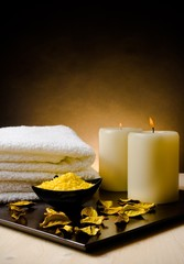 Spa massage with towel stacked, perfumed leaves and sea salt