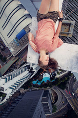 Young girl lying on the edge of a skyscraper